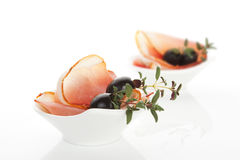 Gourmet food. Prosciutto and black olives. Royalty Free Stock Image
