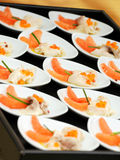 Gourmet fresh smoked salmon appetisers. Tray displayed on a buffet table of individual dishes of gourmet fresh smoked salmon appetisers at a catered event or Stock Photo