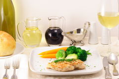Gourmet garnished grilled chicken. Delicious grilled chicken with steamed vegetables on a perfect  table set up Royalty Free Stock Images