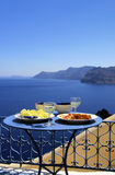 Gourmet greek food. Greek food on traditional table with view of the island of Santorini, Greece. White wine glass, fruit plate, cheese royalty free stock photos