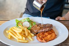 Gourmet Grill Steak : men hand pouring a gravy or sauce over the Pork and chicken stake,. Salad, French fries on white dish stock images