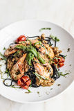 Gourmet grilled prawn and vegetables on black squid ink pasta Stock Photo