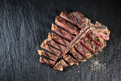 Gourmet grilled and sliced porterhouse steak. Seasoned with herbs and spices and served on a slate counter , high angle view royalty free stock photos
