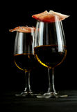 Gourmet ham balanced on glasses of Spanish sherry. For an elegant tapas appetizer, low angle over a dark background Royalty Free Stock Photo
