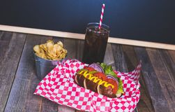 Gourmet hot dog with chips and drink in a basket with gingham na. Pkin. Tabletop, front view Royalty Free Stock Photos