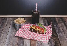 Gourmet hot dog with chips and drink in a basket with gingham na. Pkin. Tabletop, front view Stock Photos