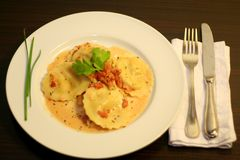 Gourmet Italian ravioli. Photograph of a yummy gourmet Italian ravioli pasta dish with creamy tomato sauce with classic white plate and silverware Stock Photography