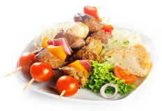 Gourmet Kebabs on Plate with Bread and Veggies Royalty Free Stock Photography