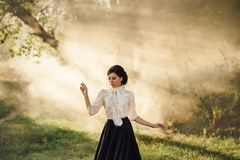 A girl in a vintage dress. Gourmet lady in a vintage dress with a frill. Walk in the fog. Artistic Photography royalty free stock images