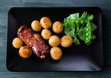 Gourmet Main Dish with roast pork ribs and fried potatoes on a b Royalty Free Stock Image