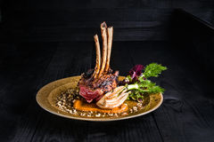 Gourmet Main Entree Course Grilled rack of lamb. Rack of lamb on a golden plate on a black background Royalty Free Stock Photo