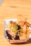 Gourmet Maine Lobster roll. On a pumpernickel bun and potato chips at the beach in summer Stock Images