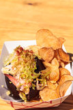 Gourmet Maine Lobster roll. On a pumpernickel bun and potato chips at the beach in summer Royalty Free Stock Photo