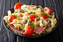 Gourmet meal: Fettuccine pasta with fried tuna steak and vegetables closeup. horizontal. Gourmet meal: Fettuccine pasta with fried tuna steak and vegetables royalty free stock photography