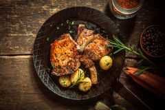 Gourmet meal of marinated pork cutlets. Served with boiled baby jacket potatoes seasoned with fresh herbs in an old frying pan on a rustic wooden kitchen table Stock Photos