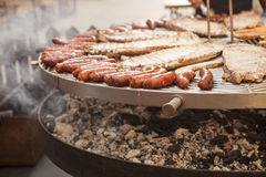 Gourmet meat pieces pork ribs, sausages, on a large grill . Stock Image