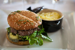 Gourmet Organic Cheeseburger. With goat cheese on a sesame bun with mashed potatoes royalty free stock image