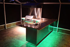 Clean Outdoor Kitchen Grill on Patio. Gourmet clean outdoor kitchen grill on patio with green lighting Stock Photo