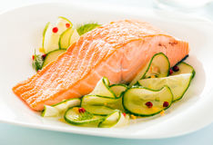Gourmet oven-baked pink salmon steak. Served with thinly sliced cucumber as a delicious seafood starter to a dinner royalty free stock image