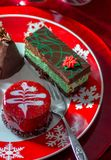 Gourmet pastries on a holiday plate. Gourmet pastries look delicious on a red snow flake plate. a mint and chocolate torte, a red glazed cappachino chocolate Royalty Free Stock Images