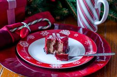 Gourmet pastry with holiday setting. A gourmet chocolate and raspberry pastry with candy cane on a beautiful holiday place setting with snow flake plate and red Royalty Free Stock Images