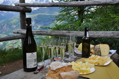 Gourmet pick nick in the mountains. Prosecco, bread and cheese. Prosecco wine and fontina cheese pick nick. Gourmet mountain food tasting. Italian Alps, local stock image