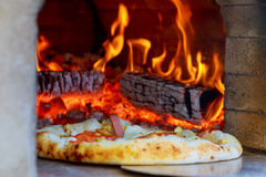 Gourmet Pizza coming out wood fired Pizza Oven in restaurant. Gourmet Pizza coming out of wood fired Pizza Oven in restaurant Stock Image