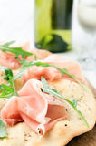 Gourmet pizza with proscuitto and wine Royalty Free Stock Image