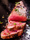 Gourmet portion of rare roast beef fillet. Garnished with chopped fresh herbs carved ready for serving for a delicious dinner Stock Images