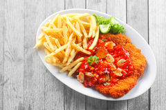 Gourmet Potato Fries and Saucy Escalope on Table Royalty Free Stock Photo