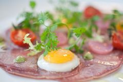 Gourmet presentation of Bacon and Eggs. With tiny eggs and large circles of bacon Royalty Free Stock Images