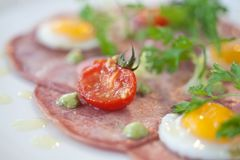 Gourmet presentation of Bacon and Eggs. With tiny eggs and large circles of bacon Royalty Free Stock Photography