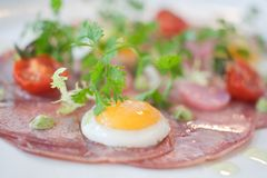 Gourmet presentation of Bacon and Eggs. With tiny eggs and large circles of bacon Stock Photography