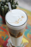 Gourmet refresh layered ice latte with leaf design whipped cream Stock Photos