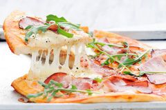 Gourmet rustic pizza lifted royalty free stock photography