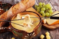 Gourmet- schweizisk fonduematst?lle p? en vinterafton med blandade ostar p? ett br?de tillsammans med en upphettad kruka av ostfo arkivfoto