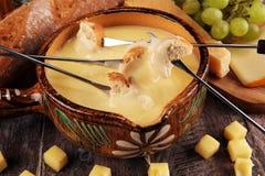 Gourmet- schweizisk fonduematst?lle p? en vinterafton med blandade ostar p? ett br?de tillsammans med en upphettad kruka av ostfo royaltyfria foton