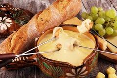 Gourmet- schweizisk fonduematst?lle p? en vinterafton med blandade ostar p? ett br?de tillsammans med en upphettad kruka av ostfo royaltyfri fotografi