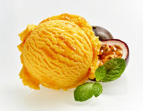 Gourmet scoop of colorful granadilla ice cream. Gourmet scoop of colorful orange granadilla ice cream with a fresh halved fruit showing the pulp behind and sprig Royalty Free Stock Photography