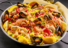 Gourmet seafood paella with prawns and mussels. Gourmet seafood paella with pink marine prawns and mussels on yellow saffron rice with peas and bell peppers Royalty Free Stock Images
