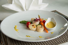 Gourmet seared scallops with garnishes. Stock Photos