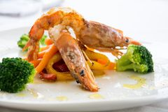 Gourmet shrimps in a restaurant. Refined plate of shrimps with broccoli, cabbage and carrots. All served in a white dish Royalty Free Stock Photo