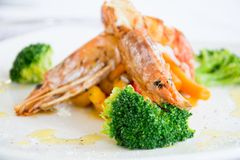 Gourmet shrimps in a restaurant. Refined plate of shrimps with broccoli, cabbage and carrots. All served in a white dish Stock Images