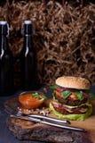 Gourmet- smaklig biffhamburgare med nötköttkotletter på ett trämagasin med öl och ketchup Arkivbild