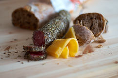 Gourmet Snack. Gouda cheese paired with French oregano salami and brown bread with nuts. Gourmet snack stock photography