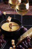 Gourmet Swiss fondue dinner on a winter evening with assorted ch. Eeses on a board alongside a heated pot of cheese fondue with two forks dipping bread and white Stock Photography