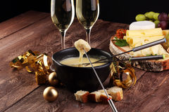 Gourmet Swiss fondue dinner on a winter evening with assorted cheeses on a board alongside a heated pot of cheese fondue with two. Forks dipping bread and white Royalty Free Stock Images