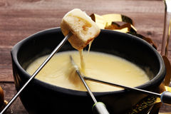 Gourmet Swiss fondue dinner on a winter evening with assorted cheeses on a board alongside a heated pot of cheese fondue with two. Forks dipping bread and white Royalty Free Stock Photos