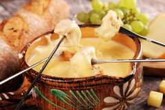 Gourmet Swiss fondue dinner on a winter evening with assorted cheeses on a board alongside a heated pot of cheese fondue with two. Forks dipping bread behind in stock photo