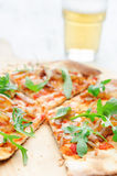 Gourmet thin crust pizza with fresh rocket and caramelised onion Stock Photo